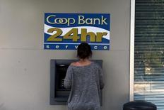 """Subir los impuestos es """"contraproducente"""" cuando un país trata de reducir la proporción entre la deuda pública y la producción económica, de acuerdo con un artículo de investigación publicado por el Banco Central Europeo (BCE) el lunes y basado en la historia reciente de la zona euro. En la imagen, una mujer realiza una transacción en un cajero fuera de una sucursal de Co-Op Bank en Nicosia, Chipre, el 15 de octubre de 2015. REUTERS/Yiannis Kourtoglou"""