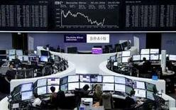 Traders work at their desks in front of the German share price index, DAX board, at the stock exchange in Frankfurt, Germany, February 9, 2016.     REUTERS/Staff/Remote