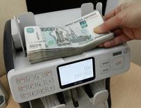 Кассир пересчитывает 1000-рублевые банкноты. Рубль торгуется в плюсе на торгах среды, получив в начале сессии поддержку от роста нефти Brent с двухнедельных минимумов и перед выступлением главы ФРС США, заранее опубликованные тезисы которого вкупе с утратой нефтью внутридневного преимущества были проигнорированы российским валютным рынком, на котором, по оценкам участников, уже появились продавцы валюты под уплату февральских налогов. REUTERS/Ilya Naymushin
