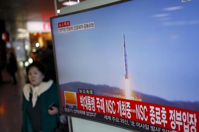 A passenger walks past a TV screen broadcasting a news report on North Korea's long range rocket launch at a railway station in Seoul, South Korea, February 7, 2016.   REUTERS/Kim Hong-Ji