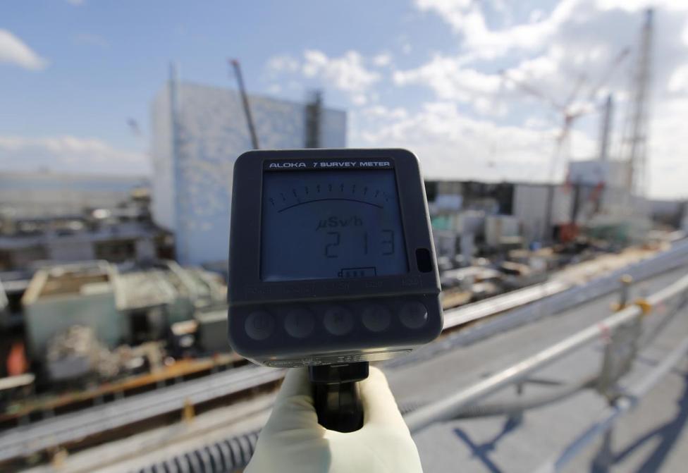 福島第1原発の第2号機(左)の近くで放射線量を測定する東電職員。毎時213マイクロシーベルトと表示された。2月10日撮影(2016年 ロイター/Toru Hanai)