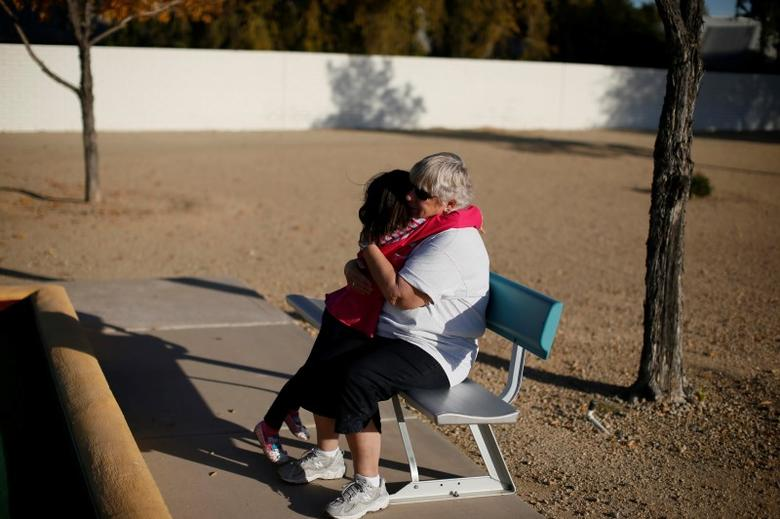 A child and a senior citizen embrace in Sun City, Arizona, January 2013. REUTERS/Lucy Nicholson