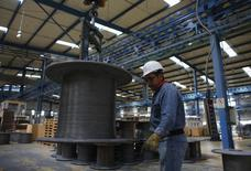Un trabajador revisa un cable de acero en la planta de TIM en Huamantla, México, oct 11, 2013. La actividad industrial de México se contrajo levemente en diciembre y completó tres meses consecutivos de declive, resaltando la debilidad de uno de los motores de la segunda economía de América Latina.  REUTERS/Tomas Bravo