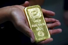 Una mujer sostiene una barra de oro de un kilogramo, en la sede de Australian Bullion Company, en Sídney, Australia. 19 de abril de 2013. Los precios del oro hacían una pausa el viernes luego de escalar un 4 por ciento el día anterior, aunque todavía se aprestaban a cerrar su mejor semana en cuatro años debido a que las turbulencias del mercado de acciones llevaron a los inversores a adquirir más activos de refugio. REUTERS/Daniel Munoz/Files