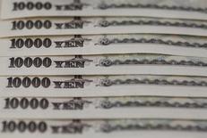 Банкноты в 10.000 иен. Иена может показать крупнейший недельный прирост против доллара с конца 2008 года в пятницу, так как беспокойства относительно мирового роста экономики обеспечили привлекательность безопасных активов, однако резкое укрепление валюты остановилось на торгах в Лондоне.     REUTERS/Shohei Miyano