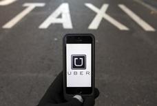 Иконка приложения Uber на экране смартфона на фоне выделенной для такси полосе в Мадриде. 10 декабря 2014 года. Компания российского бизнесмена Михаила Фридмана и партнеров LetterOne (L1) сообщила в пятницу, что сделала стратегические инвестиции в размере $200 миллионов в сервис Uber. REUTERS/Sergio Perez