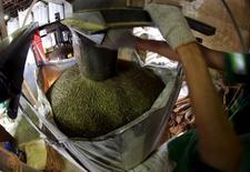 Trabalhador enche saca de café para exportação no porto de Santos. 10/12/2015 REUTERS/Paulo Whitaker