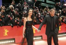 Cast member George Clooney and his wife Amal arrive on the red carpet for the screening of the movie 'Hail, Caesar!', during the opening gala of the 66th Berlinale International Film Festival, in Berlin, Germany February 11, 2016.      REUTERS/Fabrizio Bensch