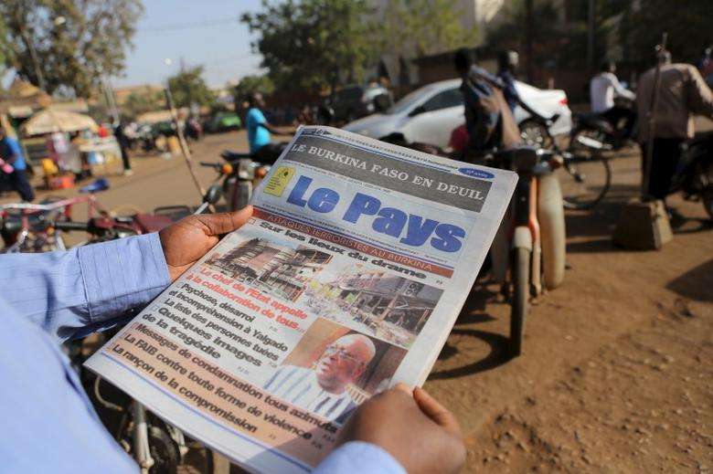 A man reads newspaper headlines that talk about the al Qaeda attack on the Splendid Hotel and Cappuccino that killed at least 28 people from at least seven countries in Ouagadougou, Burkina Faso, January 18, 2016. REUTERS/Joe Penney