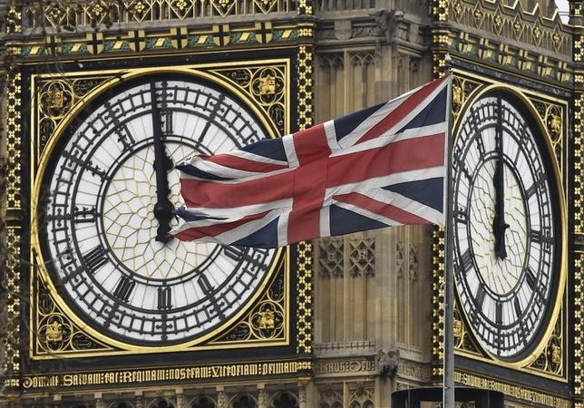 A British Union Jack flag is seen flying near a face of the clocktower at the Houses of Parliament in London, Britain, February 1, 2016. REUTERS/Toby Melville