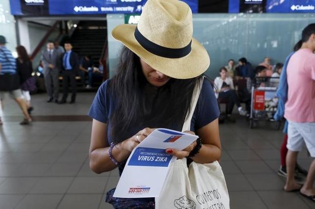 2月15日、米国務省OSACが実施した調査によると、米多国籍企業や大学、非営利団体の38%が、女性の従業員・職員に対し、ジカ熱流行国への渡航を避ることや、流行国からの出国を認めている。チリ・サンチアゴ国際空港でジカウィルスのパンフレットを読む女性。1月撮影(2016 ロイター/S/Ivan Alvarado)