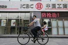 Люди едут на велосипеде мимо отделения Industrial and Commercial Bank of China Ltd (ICBC) в Пекине. Китайские банки, вооружившись новыми квотами, в январе выдали кредиты на рекордную сумму 2,51 триллиона юаней ($385,40 миллиарда), сильно превысив ожидания рынка и указав на то, что Пекин сохраняет мягкую монетарную политику для борьбы с затянувшимся замедлением экономики. REUTERS/Jason Lee