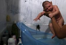 Даниэль Сантуш, 29 лет, держит в руках своего двумесячного сына, у которого диагностирована микроцефалия. Ресифи, Бразилия, 9 февраля 2016 года.  Страны, столкнувшиеся с вирусом Зика, должны искать новые пути борьбы с комарами, переносящими это заболевание, сообщила Всемирная организация здравоохранения, предложив создавать генетически модифицированных насекомых и бактерии, препятствующие выводу их личинок. REUTERS/Nacho Doce