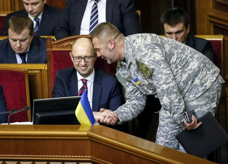 A member of parliament shakes hands with Prime Minister Arseny Yatseniuk (2nd L) during a parliament session in Kiev, Ukraine, February 16, 2016.    REUTERS/Gleb Garanich