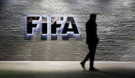 A journalist walks in front of FIFA's headquarters in Zurich, Switzerland December 2, 2015.    REUTERS/Arnd Wiegmann