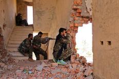 """Бойцы курдских Отрядов народной самообороны (YPG) на своих позициях в разрушенном доме в сирийском городе Хасака. 22 июля 2015 года. Президент Турции Тайип Эрдоган сказал во вторник, что """"безжалостная операция"""" России и сирийского правительства на севере Сирии, где их силы продвинулись к турецкой границе, направлена на создание коридора для курдских боевиков. REUTERS/Rodi Said"""