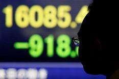 Un peatón mira un tablero electrónico que muestra el índice Nikkei de Japón, afuera de una correduría en Tokio, Japón. 9 de febrero de 2016.Las acciones japonesas cayeron en una sesión volátil el miércoles por un fortalecimiento del yen, luego de que un rebote de los precios del crudo perdió impulso, lo que revivió la demanda por la moneda japonesa. REUTERS/Yuya Shino
