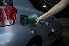 Una persona carrgando combustible en una gasolinera de PDVSA en Caracas, feb 13, 2016. El mundo del petróleo ha sido remecido esta semana por el acuerdo de algunos grandes productores para congelar sus volúmenes de extracción en los niveles de enero y contener el exceso de suministros que ha mermado los precios, pero los mercados indican que los inversores dudan de la estrategia.  REUTERS/Marco Bello