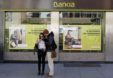 Bankia decidió abrir el miércoles un proceso para devolver a los inversores minoristas toda la inversión realizada en su salida a bolsa de 2011 más intereses, en un intento por zanjar una disputa judicial y abaratar sus costes asociados. En la imagen, unos turistas consultan un mapa frente a una sucursal de Bankia en Sevilla, el 17 de febrero de 2016. REUTERS/Marcelo del Pozo