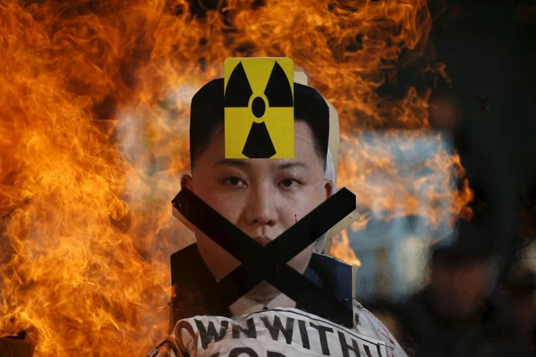 A cut-out of North Korean leader Kim Jong Un is set on fire during an anti-North Korea rally in central Seoul, South Korea, February 11, 2016. REUTERS/Kim Hong-Ji