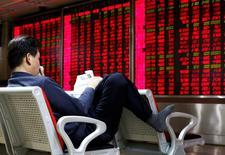 Un inversor lee un diario frente a un tablero electrónico que muestra información bursátil, en una correduría en Pekín, China, 16 de febrero de 2016. El rebote del mercado de valores de China mostró señales de fatiga el jueves cuando los principales índices cedieron unos  avances iniciales y cerraron a la baja por una toma de ganancias. REUTERS/Kim Kyung-Hoon
