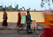 Продавец яиц говорит по телефону у буддийского монастыря в Индии. 23 декабря 2014 года. Индийский производитель мобильных телефонов Ringing Bells в четверг начал продажу смартфона стоимостью $4, однако через несколько часов она была приостановлена, так как огромный спрос вызвал сбой на сайте малоизвестной компании. REUTERS/Abhishek N. Chinnappa