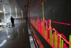 Инвестор смотрит на экран, демонстрирующий информацию о торгах на китайском рынке акций.  Рынок акций Китая завершил торги пятницы снижением вслед за коррекцией мировых фондовых площадок, однако основные индексы продемонстрировали солидный рост за неделю. REUTERS/Kim Kyung-Hoon
