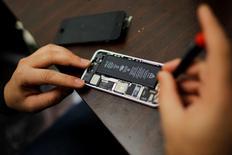 Un trabajador intenta reparar un iPhone en una tienda en Nueva York, 17 de febrero de 2016. Apple probablemente invocará los derechos de libertad de expresión en Estados Unidos como unos de sus principales argumentos legales para impedir la orden judicial de desbloquear el iPhone encriptado de uno de los autores del ataque mortal en San Bernardino, dijeron esta semana abogados con experiencia en la materia. REUTERS/Eduardo Munoz