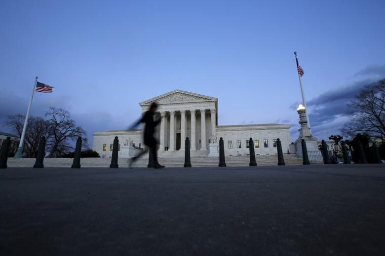A woman walks past the Supreme Court building at Capitol Hill in Washington D.C., February 13, 2016.   REUTERS/Carlos Barria