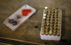 """Коробка с патронами и iPhone в стрелковом клубе Лос-Анджелеса 23 января 2013 года. Министерство юстиции США подало ходатайство в пятницу, чтобы заставить Apple Inc подчиниться постановлению суда о взломе закодированного iPhone, принадлежавшего одному из стрелков из Сан-Бернардино, назвав отказ технологического гиганта """"маркетинговым ходом"""". REUTERS/Lucy Nicholson"""