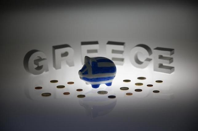 A piggybank painted in the colours of the Greek flag stands amongst various euro coins in front of letters spelling the word 'GREECE' in this picture illustration taken in Berlin, Germany June 30, 2015. REUTERS/Pawel Kopczynski