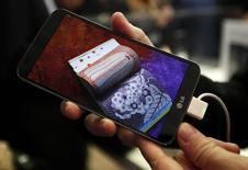 LG Electronics presentó su primer teléfono inteligente modular, con un sistema de sonido B&O y lente gran angular, en la reunión anual del Mobile World Congress en Barcelona. En la imagen, una persona sujeta un G Flex de LG Electronics durante el Mobile World Congress (MWC) en Barcelona, 24 de febrero de 2014. REUTERS/Gustau Nacarino