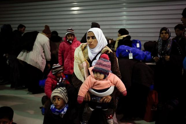 A woman holds her two children inside a terminal, following the arrival of refugees and migrants aboard the passenger ferry Blue Star Patmos at the port of Piraeus, near Athens, Greece, February 22, 2016. REUTERS/Alkis Konstantinidis