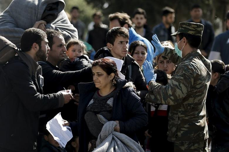 A Greek military officer (R) checks the documents of refugees before allowing them to exit a relocation camp for refugees and travel to the Greek-Macedonian border in Schisto, near Athens, Greece, February 23, 2016. REUTERS/Alkis Konstantinidis