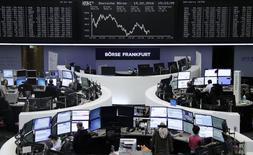 Traders work at their desks in front of the German share price index, DAX board, at the stock exchange in Frankfurt, Germany, February 19, 2016. REUTERS/Staff/Remote