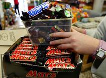 Mars Inc ha retirado chocolatinas y otros productos en 55 países, principalmente en Europa, después de que un trozo de plástico apareciera en una barrita de Snickers en Alemania, dijo el martes el fabricante. En la foto de archivo, un empleado retira barritas de Mars y Snickers en una tienda en Sídney el 2 de julio de 2005. REUTERS/Will Burgess/Files