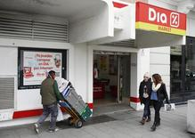 La cadena de distribución DIA anunció el miércoles unos resultados anuales en línea con las previsiones del mercado, y confirmó que prevé que sus ventas en espacio comparable en España y Portugal entren en terreno positivo en el segundo trimestre del año. En la imagen, varias personas pasan junto a un supermercado de DIA en Madrid, el 23 de febrero de 2015. REUTERS/Juan Medina