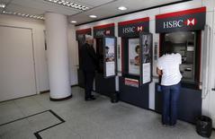 Imagen de archivo de unas personas utilizando unos cajeros automáticos en una sucursal del banco HSBC en Río de Janeiro, jun 9, 2015. Los créditos bancarios impagos por al menos 90 días en Brasil subieron en enero a un máximo en más de tres años, dijo el Banco Central el miércoles, mientras que la peor recesión en décadas y el aumento del costo de endeudamiento presionaba la capacidad de los prestatarios para mantenerse al día en el pago de deudas.    REUTERS/Sergio Moraes