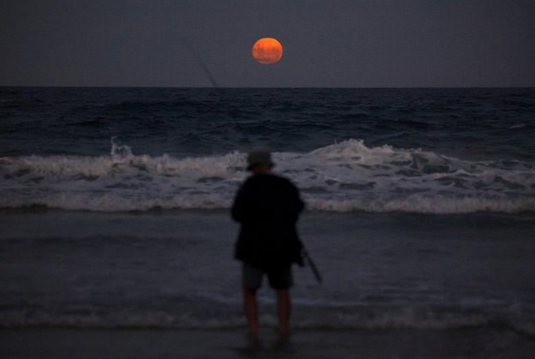 A fisherman prepares to cast his line standing in the surf as a full moon rises at Mollymook Beach, located south of Sydney, Australia, February 23, 2016.    REUTERS/David Gray