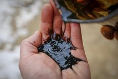 Рабочий нефтяного месторождения РД Казмунайгаз льет нефть себе на ладонь. Кызылординская область, 22 января 2016 года.  Казахстан, страдающий от падения мировых цен на нефть и металлы, в 2016 году ждет значительного роста дефицита бюджета, но не предполагает занимать для его финансирования, сказал в четверг депутатам Сената сказал министр национальной экономики Ерболат Досаев. REUTERS/Shamil Zhumatov