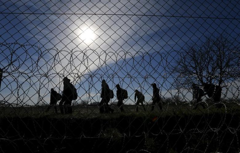 Migrants walk along Hungary's border fence on the Serbian side of the border near Morahalom, Hungary, February 22, 2016. REUTERS/Laszlo Balogh