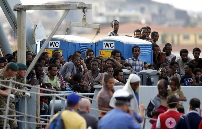 2月25日、ドイツ連邦議会(下院)は、中東などから押し寄せる難民の流入を抑制するための法案を可決した。写真は中東からシチリア島に上陸した難民ら。2015年10月撮影(2016年 ロイター/Antonio Parrinello)