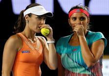 Switzerland's Martina Hingis (L) and India's Sania Mirza react during their doubles final match at the Australian Open tennis tournament at Melbourne Park, Australia, January 29, 2016. REUTERS/Issei Kato