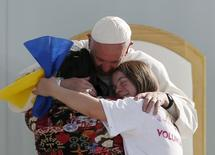 Pope Francis hugs two girls during a meeting with youths at the Jose Maria Morelos y Pavon stadium in Morelia, Mexico, February 16, 2016. REUTERS/Carlos Garcia Rawlins