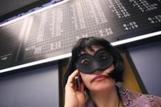Трейдер фондовой биржке в полумаске перед табло с индексами Франкфуртской биржи акций 16 февраля 2010 года. Балтийская биржа подтвердила получение нескольких заявок на покупку в пятницу после того, как Сингапурская фондовая биржа (SGX) объявила о намерении приобрести организацию, которая несколько веков была центром мирового рынка морских перевозок. REUTERS/Johannes Eisele