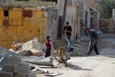 Жители чинят дом в городе Дарат-Изза провинции Алеппо 28 февраля 2016 года. Сирийская оппозиция предупредила в воскресенье, что атаки лояльной Башару Асаду армии при поддержке российских военной авиации могут привести к провалу согласованного Москвой и Вашингтоном перемирия и ставят под угрозу будущие мирные переговоры. REUTERS/Ammar Abdullah
