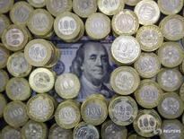 Монеты валюты тенге и долларовая купюра в Алма-Ате 6 ноября 2015 года. Центральный банк пережившего девальвацию национальной валюты Казахстана упростил правила установки обменного курса для обменников, но вдвое уменьшил сумму, в рамках которой покупатель не обязан предъявлять удостоверение личности. REUTERS/Shamil Zhumatov