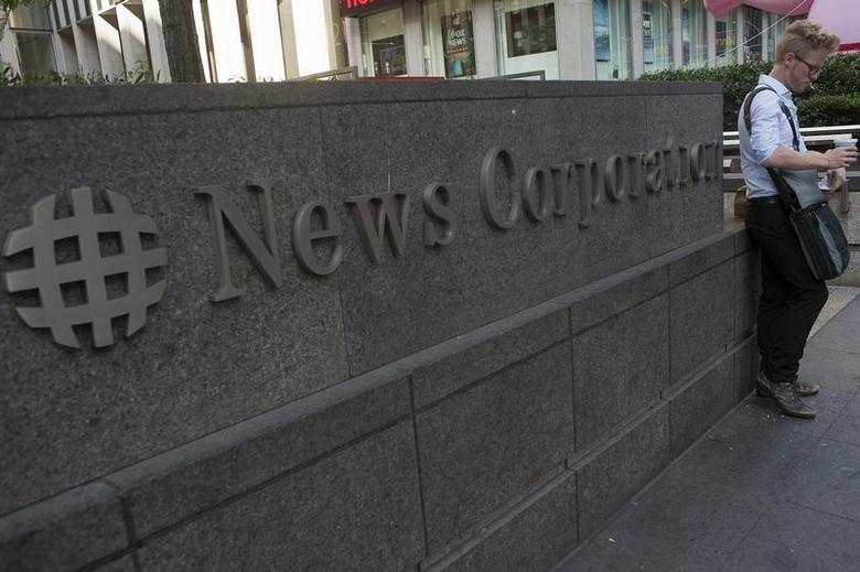 A passer-by stands in front of the News Corporation building in New York June 28, 2012. News Corp said on Thursday its board had approved a plan to split the company into two entities, and that Rupert Murdoch will remain as chief executive of its new, separate entertainment company. REUTERS/Keith Bedford (UNITED STATES - Tags: BUSINESS MEDIA LOGO) - RTR34A6S