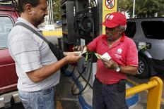 Una persona pagando tras cargar combustible en una gasolinera de PDVSA en Caracas, feb 19, 2016. La agencia calificadora Fitch Ratings dijo el lunes que las medidas económicas tomadas por el Gobierno venezolano, dentro de sus intentos por hacer frente a una aguda crisis económica, no fueron suficientes para mejorar su capacidad crediticia.  REUTERS/Marco Bello