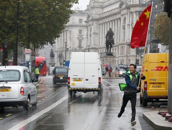 A supporters of China's President Xi Jinping runs down Whitehall with Chinese flag outside Downing Street in central London, Britain, October 21, 2015. REUTERS/Peter Nicholls/Files